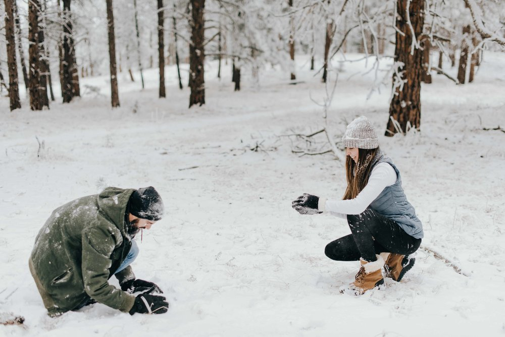 Tani and Nik in the middle of their snowball fight during their mountain engagement session in Denver, Colorado.