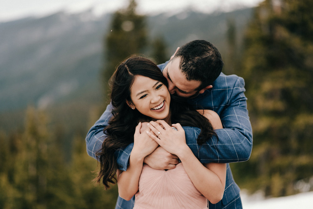 Steve whispering something funny in Celina's ear during their snowy engagement shoot.