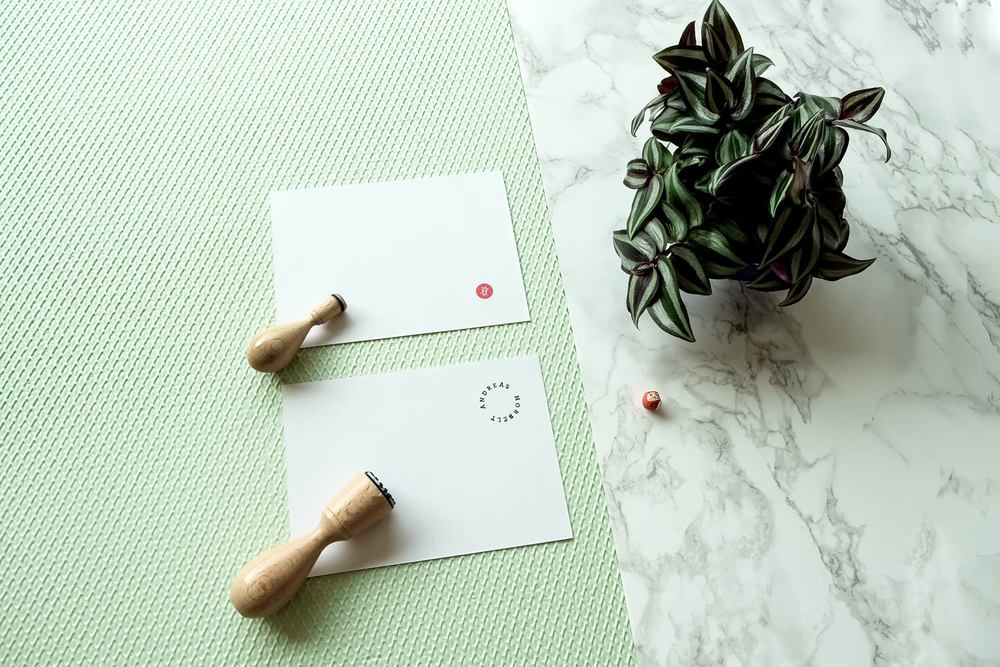 Japanese Hanko stamp, plant and greeting card on green textured surface and marble