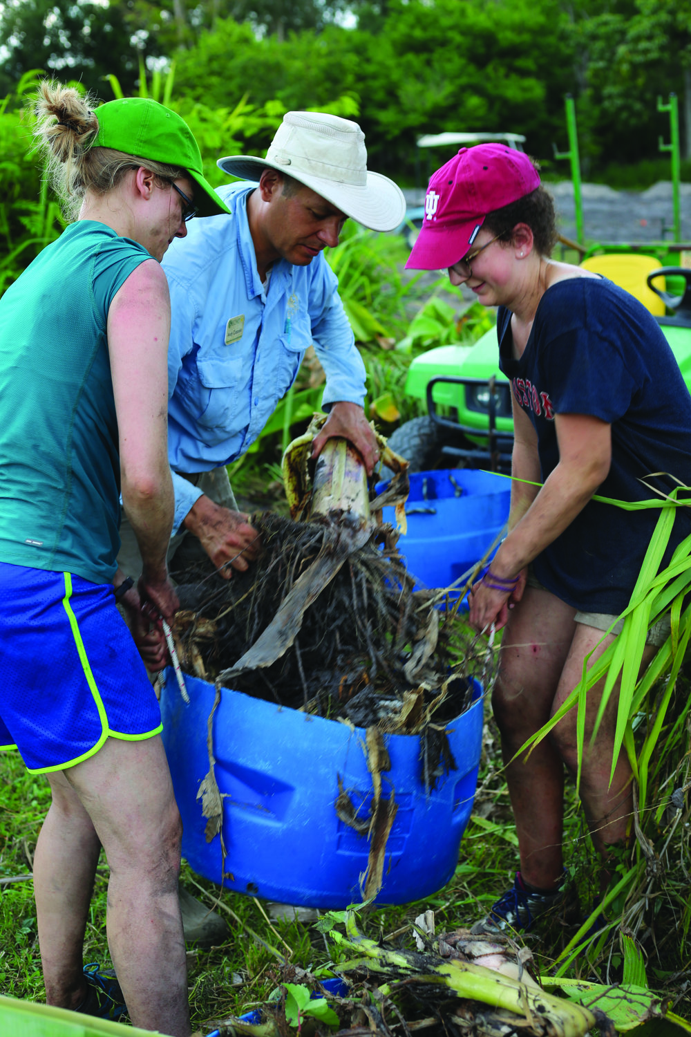 Ellen Smith (left), eight-time return volunteer from Indiana, works alongside Andy Cotarelo (center), ECHO Farm Manager, to clear a research plot at the Global Farm in North Fort Myers, Florida.