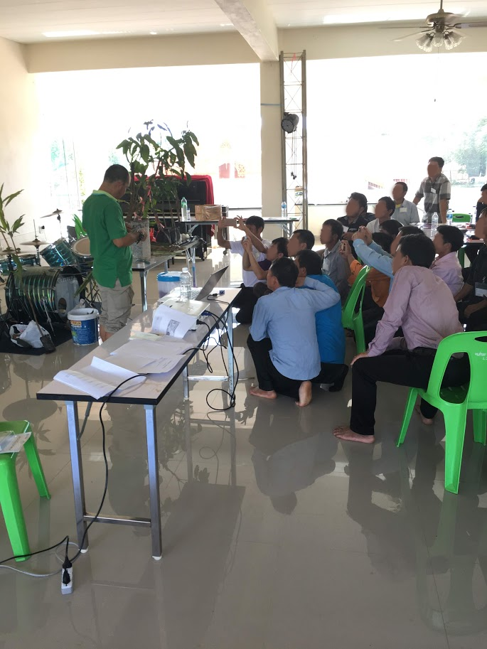 Below: Laotian pastors gather closely to ECHO farm manager Sombat as he teaches a seminar on grafting. Above: Sombat demonstrates an improved cookstove.