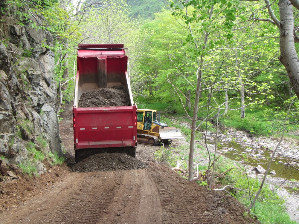Laying down a new layer of dirt to even out the trail.