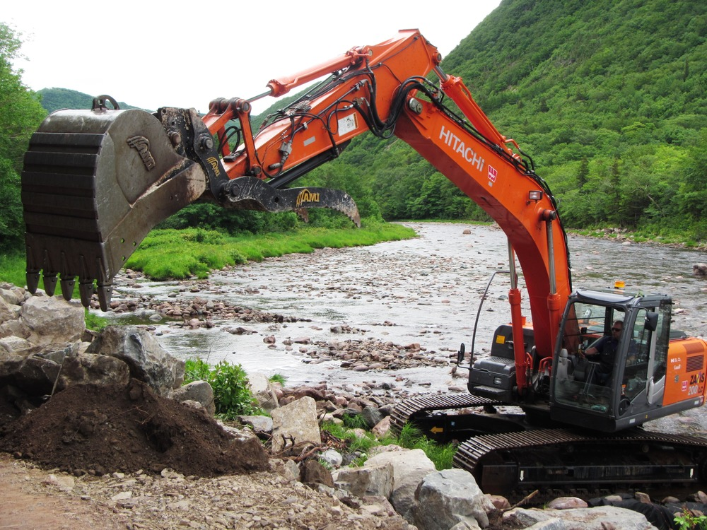 Excavator installing rock deflectors above Fence Pool