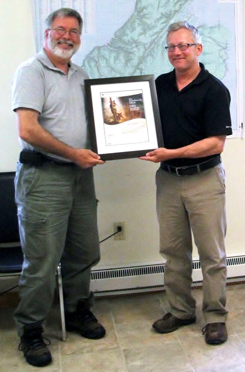 Derek Quann (Acting Superintendent for Cape Breton Highlands National Park) presenting CEO Award of Excellence to Rene Aucoin, President of the Cheticamp River Salmon Association.