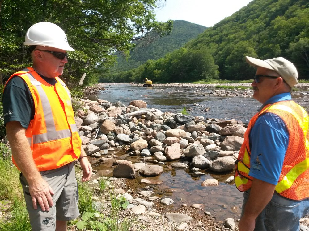 Archie Doucette (left, Parks Canada) and Charles MacInnis (project consultant in charge of restoration design and construction of instream structures) oversee work at the Faribault Brook site.