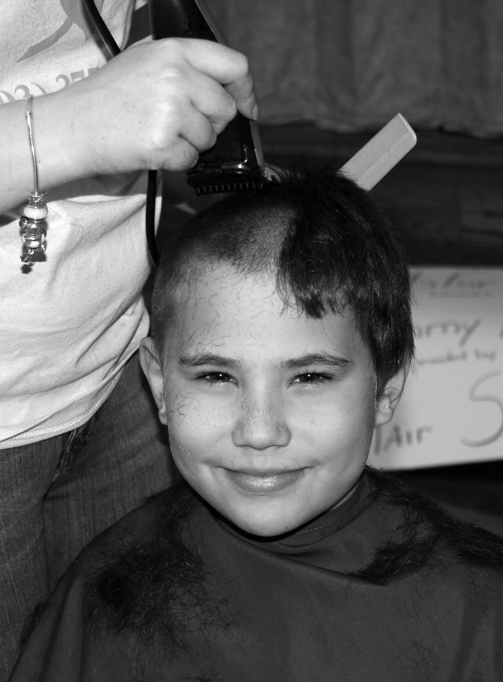 Michael Guasp cuts hair for a good cause — with a smile. Below: Schoolmate Leila Mellen offers up her pigtails as well.