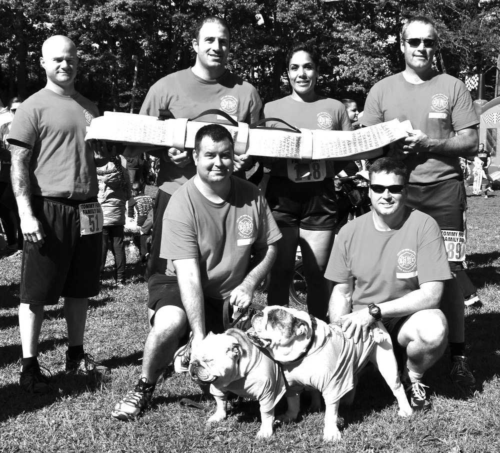 Probationary firefighters from New Haven ran the 5K carrying a heavy hose inscribed with names of firefighters who have died in the line of duty. Pictured back row: Ernie Ouellette, Daniel Del Prete, Yaniris Cardona, Kevin Reilly. Front row: Ryan Jayne, Chris Joyce, bulldogs Nellie and Buddy.