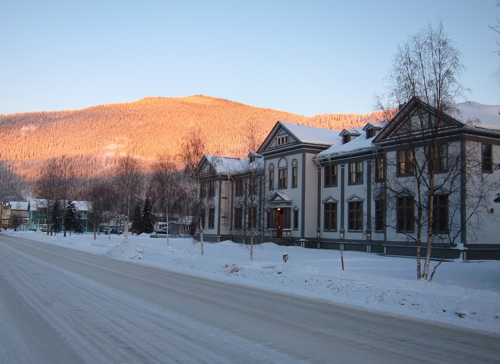 The Dawson City Museum with the Midnight Dome, illuminated by the setting sun, in the background.