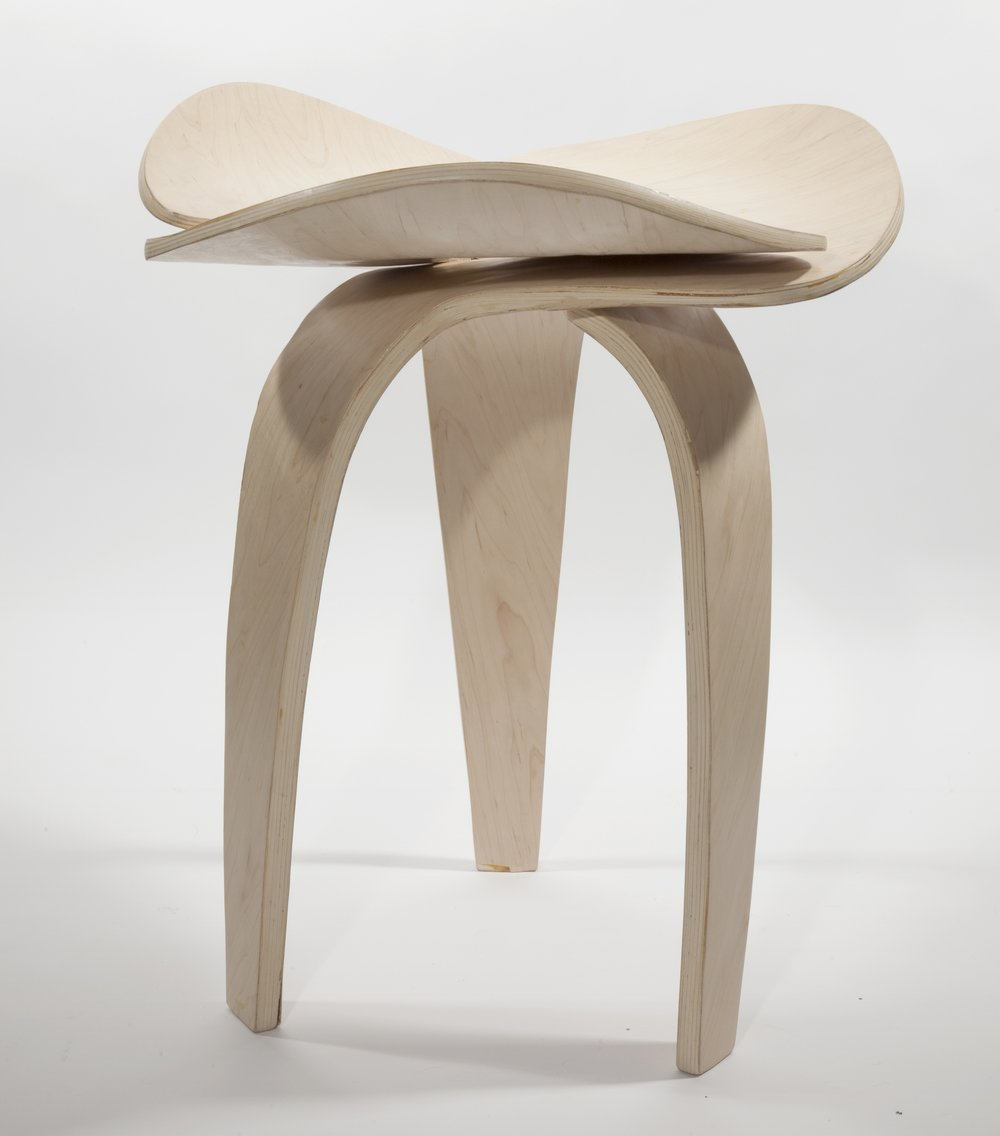 Three identical bent plywood pieces intersect and support.