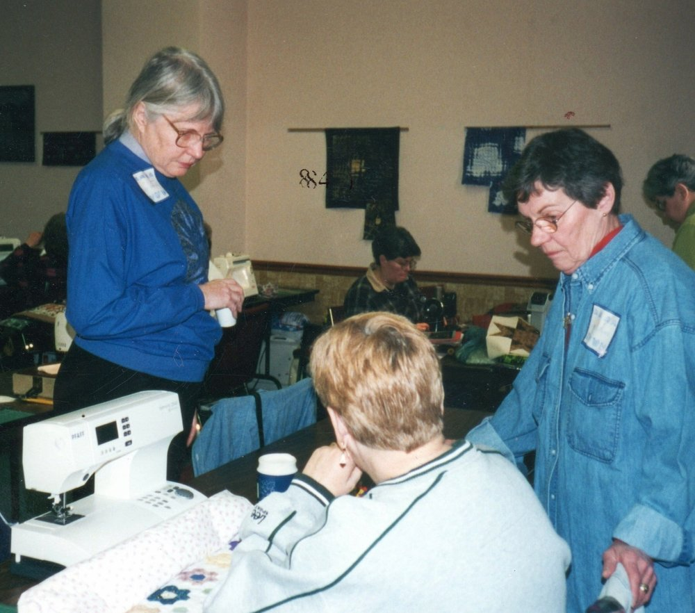 Two former VQ members: Judy Peterson (standing, left) and Dee O'Meara (standing, right) at an IQI Quilt-In.