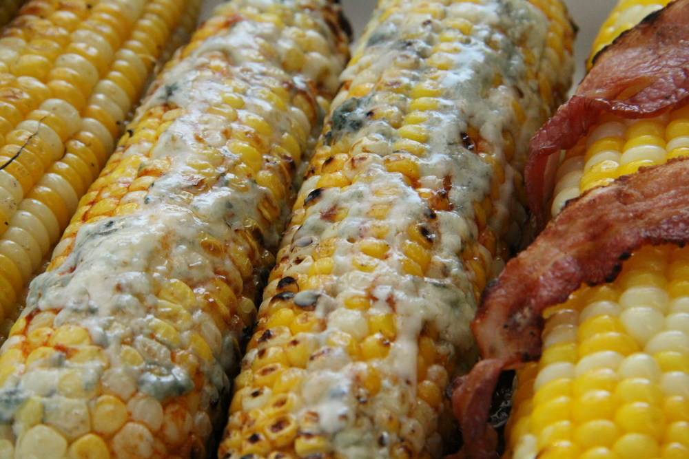 Buffalo Blue Cheese next to a Bacon wrapped grilled corn on the cob.
