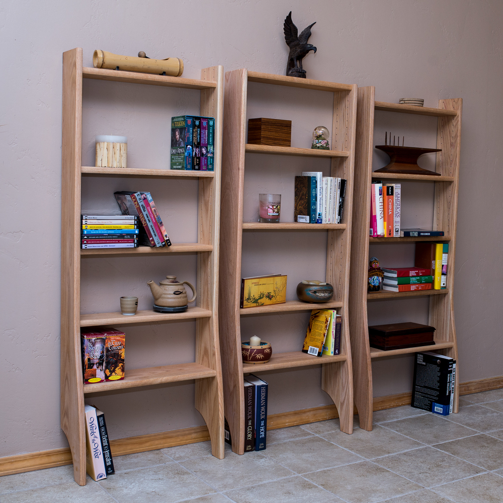 Nomad Bookcase (three shown).    Shown in Oak.   Note the cut-away for the base board.   You can put them together for a unified look.