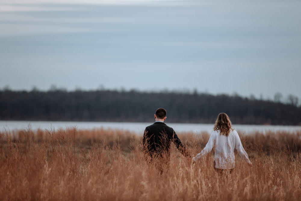 couple-walking-through-field-sunset-photos