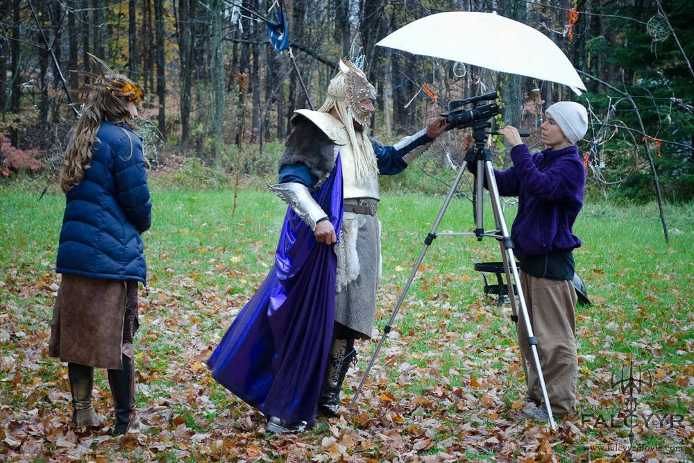 Keeping warm while they set up the camera for our scene. You can't see the rain but that is why they needed the umbrella. Photo credit: Unicovia Pictures