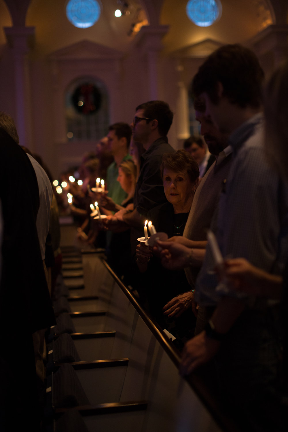 A worshipper lights the candle of the person next to her, Christmas Eve 2015.