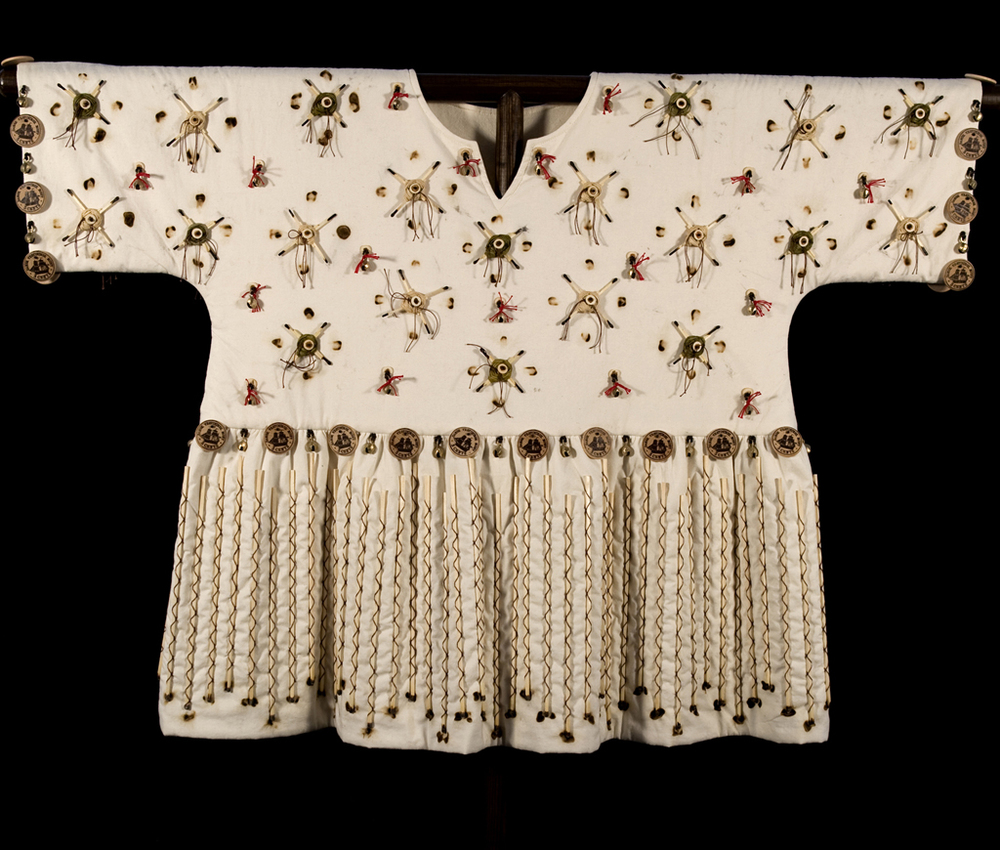 Queen Mary (Thomas) War Shirt (Danish Virgin Islands (now US Virgin Islands))    Materials:  Cotton Muslin, Cotton Batting, Stick Matches, Brass Bells, Wood Beads & Discs, Raffia, Oak, Cotton Yarn, Poly/Cotton Thread  Techniques:  Embroidery, Screen Printing, Beading, Fabric Burning, Patternmaking, Garment Construction   2009