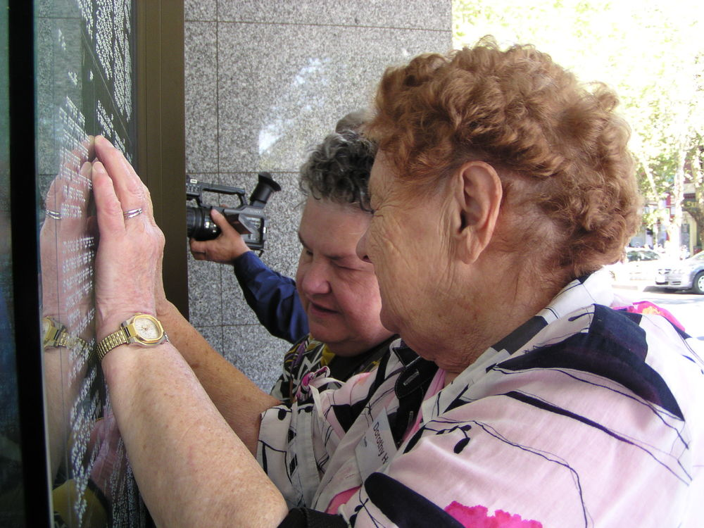 Participants reading the work produced in Braille writing workshopu