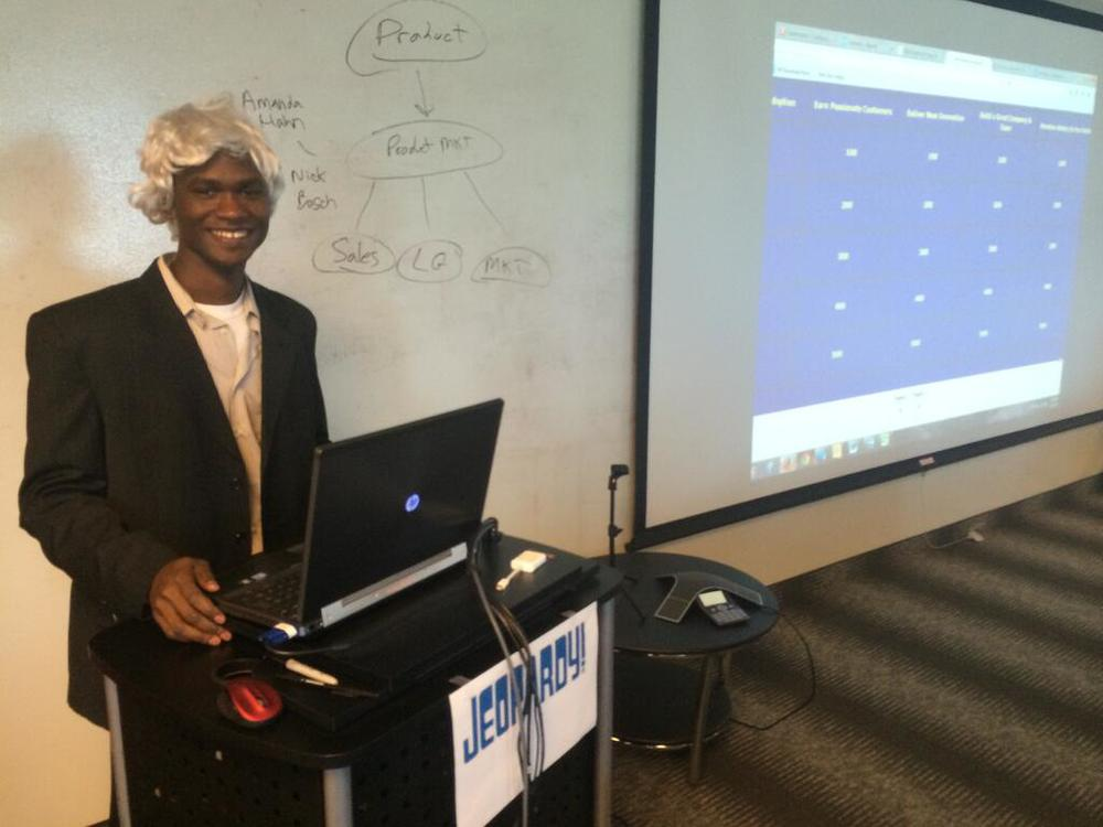 Here I am in a black suit impersonating Alex Trebek during a new hire onboarding event!