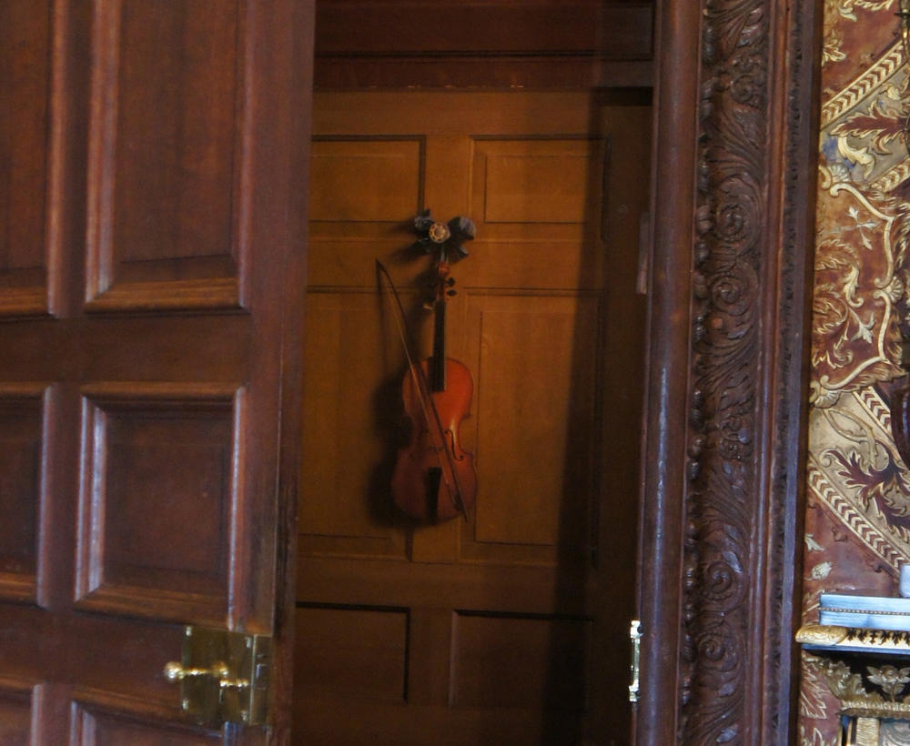 Both the interior door and the violin that hangs on it are painted and actually flat.
