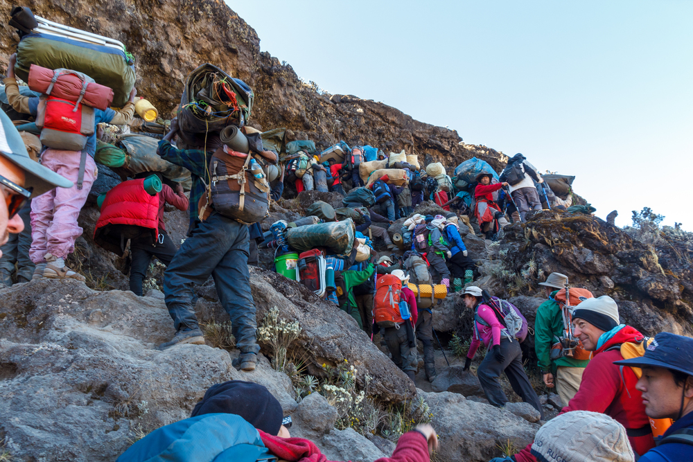 Porters traversing up the Barranco Wall 'Breakfast Wall' on Mt. Kilimanjaro - Photo Credit: Lincoln Chu