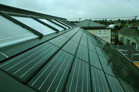 Finished roof showing the ridgeline row of solar water heating panels with the solar array below.