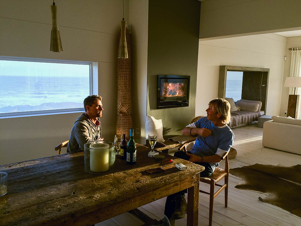 Rufus and Jochem relaxing in front of the fire, overlooking Yzerfontein beach