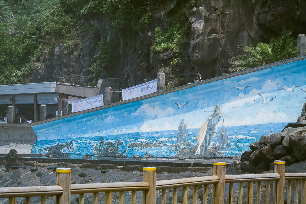intricate murals along the water's edge at Jungmun Beach