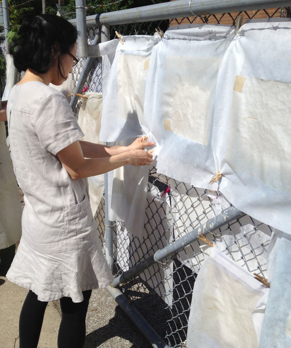 Aimee adjusting our first small papers as they dried on the fence.