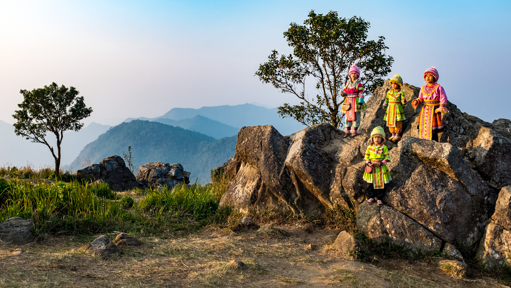 A group of girls sing together in the morning light on Phu Chi Fa.
