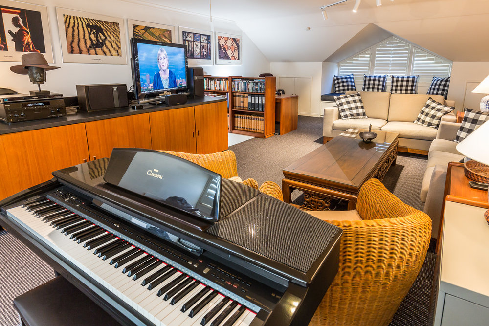 The upstairs loft with piano, flat screen TV and lounge.