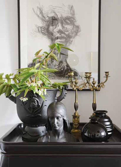 Det svarta bordet kommer från Ikeas 1700-talsserie. Tavlan är gjord av Jesper Waldersten. Urnan från Näfvekvarns bruk. Kandelabrarna är ett av Jans första antikinköp. Den räfflade vasen är från Gefle.