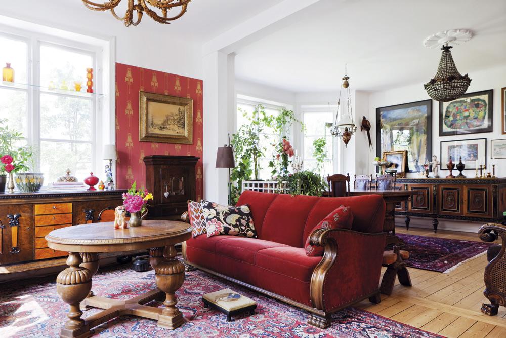 Stora rummet.Sandra föredrar stora gamla tunga möbler. Alla möbler i det här rummet är köpta på auktion. Soffan betalade Sandra 1 500 kronor för. Soffbordet med de kulformade benen är en favorit. I bakgrunden syns matbordet med en fotogenlampa över.