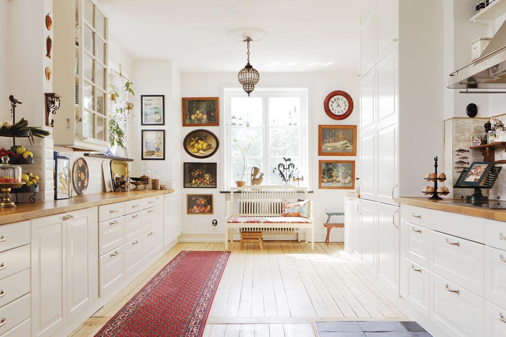 Köket. Det var från början två rum, men gjordes om till ett rejält kök. Köksskåpen är från Ikea, men de övre skåpen är gjorda av gamla fönster. Handtagen är från Byggfabriken. Vid fönstret en pinnsoffa och i fönstret en tuppastake i smide. Till höger syns en ägghållare som Sandra köpt på en loppis i Malmö. Äggen är från de egna hönsen.