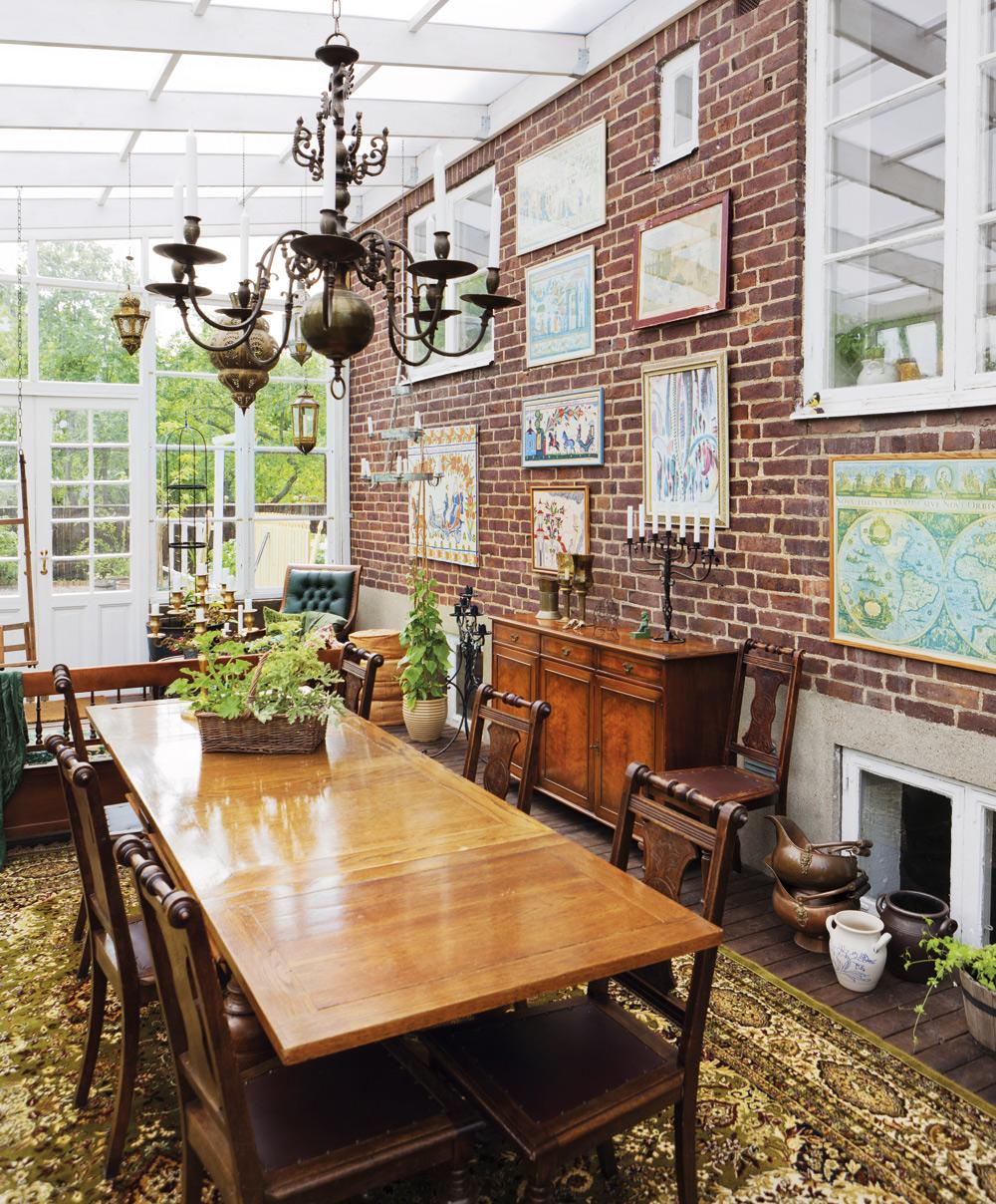 Matplatsen i vinterträdgården. Matsalsbord, stolar och ljuskrona i taket. På ytterväggen har Sandra hängt tavlor och ställt en skänk. Hon vill att känslan inne i huset ska flyta med till uterummet. Alla möbler är köpta på olika auktioner.
