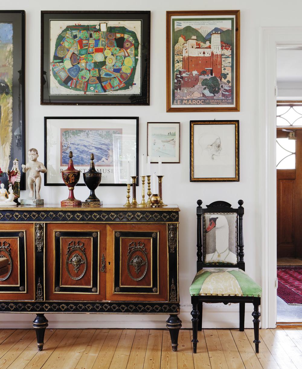 Skänk.Den är inhandlad på Lauritz.com. Det finns en likadan skänk till som har fått bli en kommod i badrummet. På väggen hänger en blandad kompott av tavlor, posters och porträtt. Den stora färgrika målningen är Sandras favoritkonstnär Huntertwasser. Det lilla porträttet över stolen föreställer Sandra. Stolen är klädd i ett tyg som tryckts med maken Klas mönster på.
