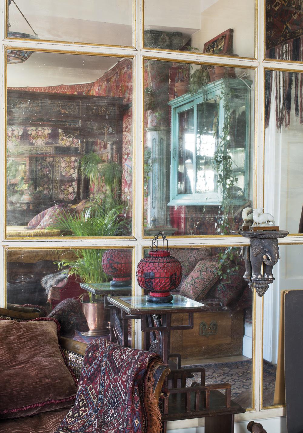 SPEGELVÄGG. Är uppsatt i sovrummet och är en av de få svenska saker som finns i hemmet. Väggen var en gång i tiden en del av inredningen hos anrika Böhlmarks. Fåtöljen är ett auktionsfynd.