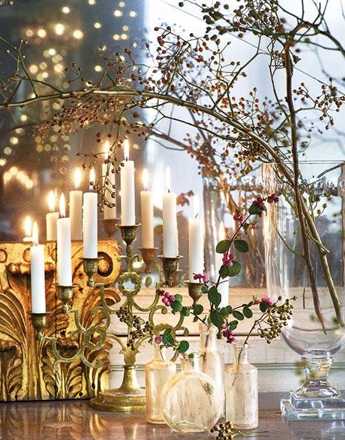 Placera kandelabrar och ljusstakar framför en spegel för att maximera effekten av ljus. Kandelaber i mässing, 250 kr och små flaskor i frostat glas, 35 kr/st, Lust & Fägring. Glasvas på fot, 2 450 kr och gulddekoration, Golden Wall Element, 2 090 kr, Oscar & Clothilde.