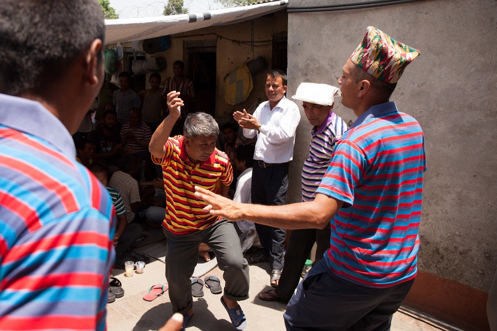 With encouragement from Indira several prisoners get up and dance to the traditional Nepali music played by the other prisoners, overseen by one of the prison staff in a white shirt and other prisoners.  The prisoner with the yellow striped T Shirt has been convicted for murder.