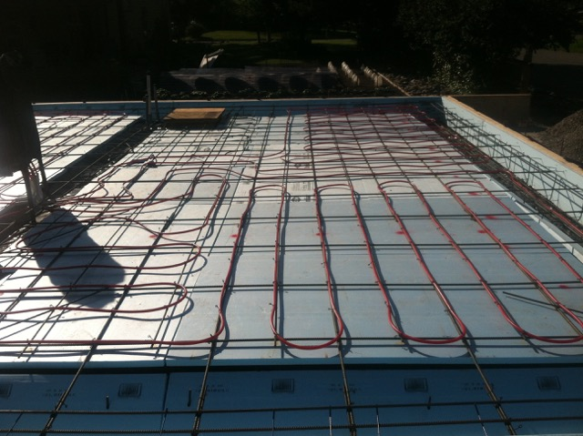 The red tubes will be embedded into the concrete.  They will run the hot water of the radiant heating system in the floor.