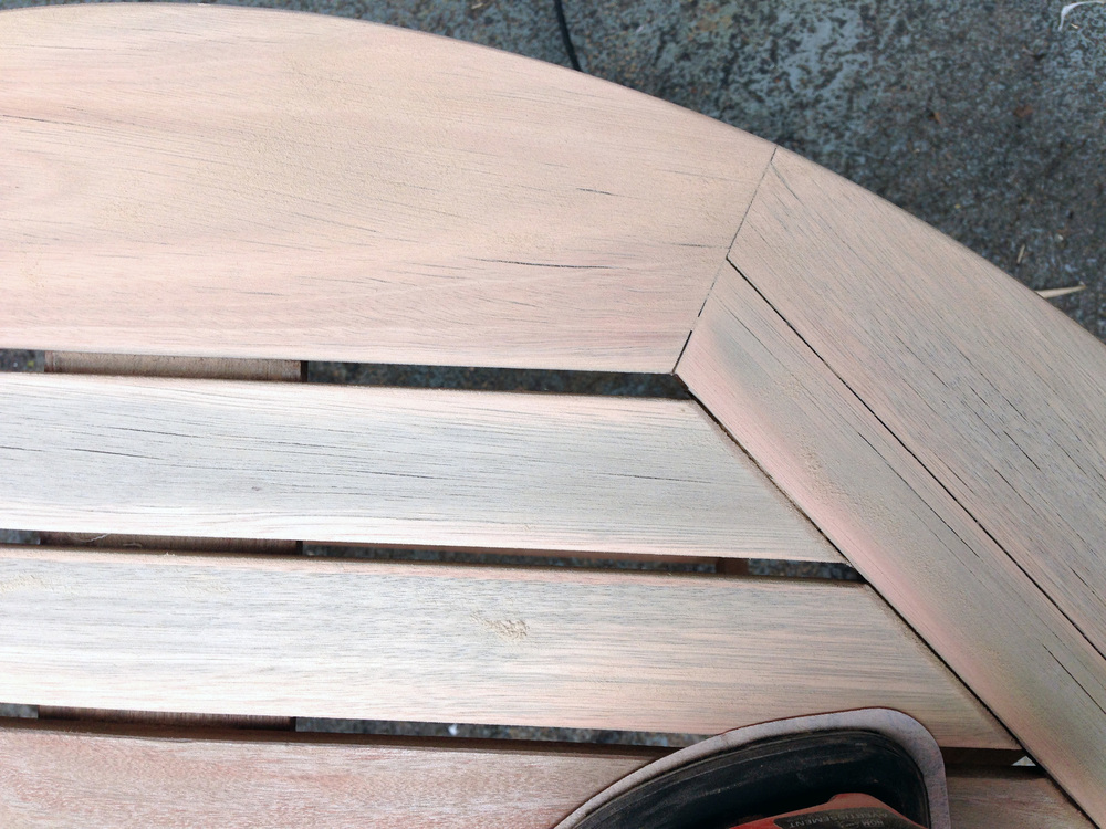 {this shows the dry grey wood being sanded away to reveal the pink wood beneath}