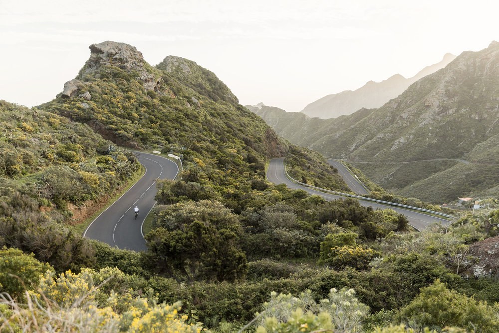 A man bikes up a winding road in Tenerife in the Canary Islands by Rebecca Stumpf, Denver Boulder Colorado Editorial and Commercial Photographer.