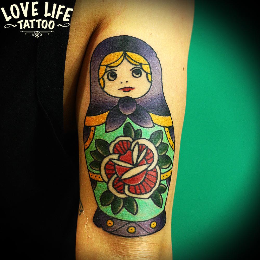 татуировка матрешки с цветком
