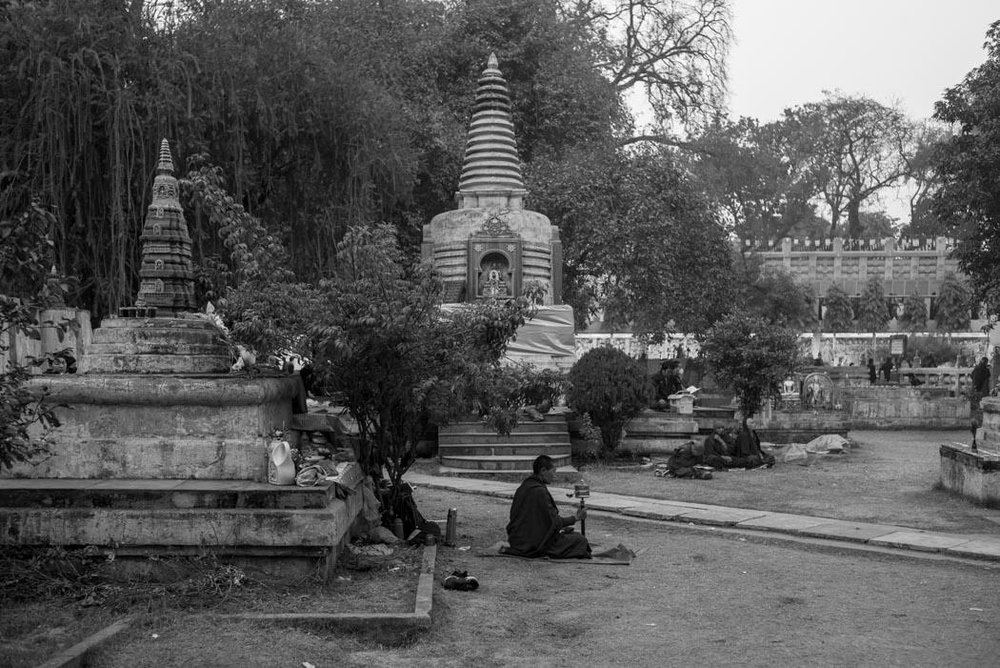 A pilgrim turning his mani wheel among the stupas on the Mahabhodi Temple grounds