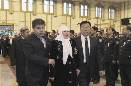 A woman is escorted at a funeral ceremony for officials who died in last week's bloody clash between residents and officials in Kashgar, April 29, 2013. Credit: REUTERS/Stringer.