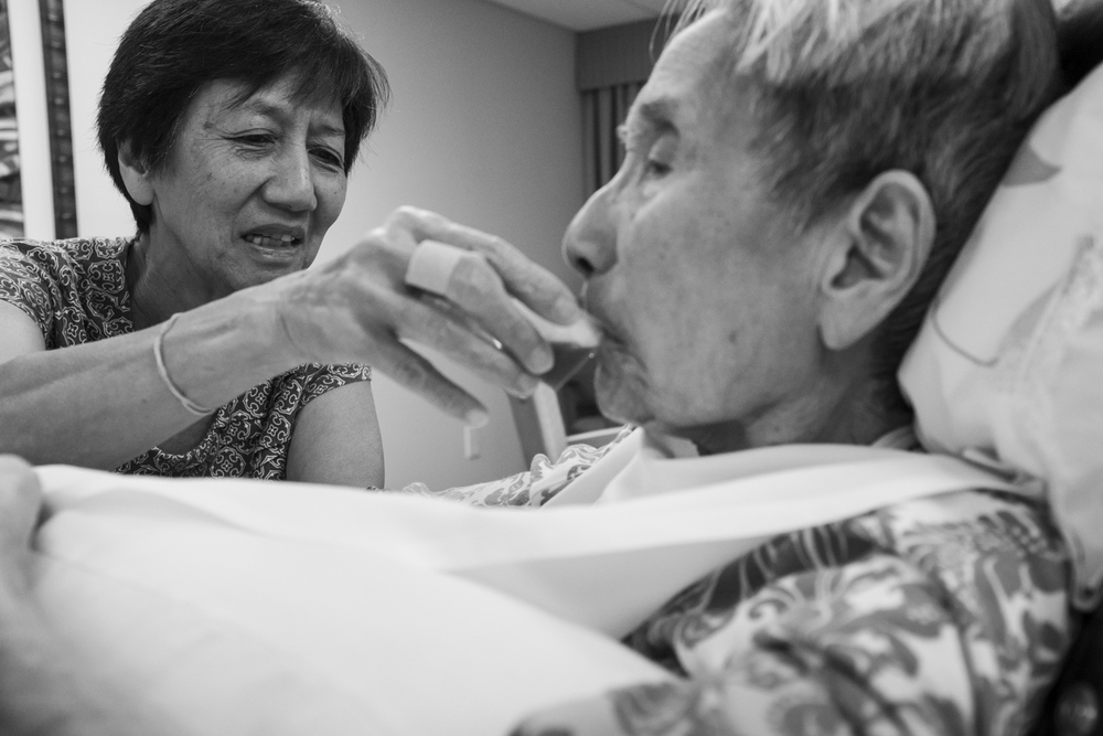 My mother, Kathy Hida, tries to feed my popo some juice to keep her hydrated. A few days before popo passed away, she stopped eating and drinking altogether.