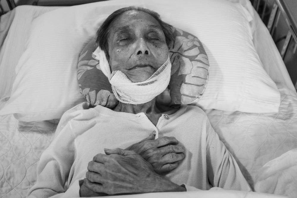 The nurses performed afterlife preparations and wrapped a gauze around popo's jaw. Popo laid peacefully with her arms crossed.