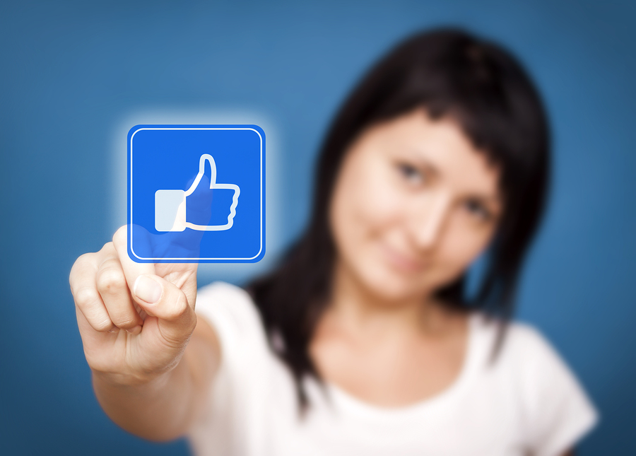 """Stock photo of woman clicking Facebook """"like"""" button."""