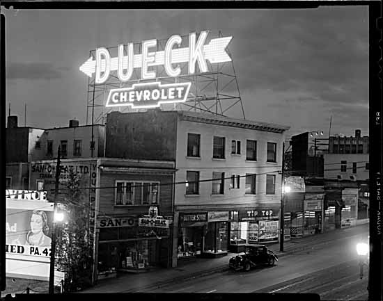 Dueck Chevrolet neon sign at night on building Granville & West Broadway. Part of a second billboard for Daily Province Newspaper also show. 1949 ©VPL Archives