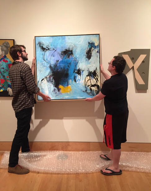 "Hanging Linda's painting, ""Laugh At The Night"" at the 2018 Texas National Exhibition at Stephen F. Austin University.    Photo courtesy of    Julie Villing   ."