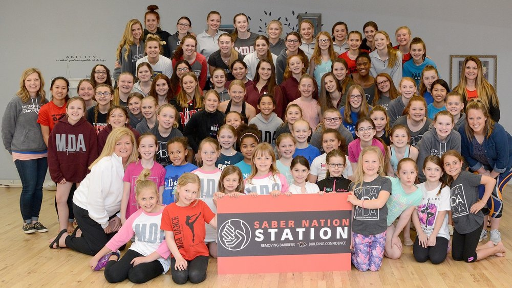 "MDA dancers attended  Midwest Starz  this past weekend, and as impressive as all the dancing, placements, and awards were, MDA is proud to announce that our dancers participated in the Starz trophy buyback program during the competition. Dancers voluntarily donated back the awards they received after each awards ceremony. Midwest Starz then provided a donation to an organization of our choice for the value of the medal and then matched that amount! Additionally, MDA matched Midwest Starz's donation for a grand total of $1,000. The organization of our choice was Saber Nation Station. Thank you to all our families for raising such strong character driven dancers who recognize the value of giving back to others. This might be the greatest overall ""high score"" to date.  Shakopee High School's Saber Nation Station is a resource room where students can access items they need to eliminate barriers to success. With the support of the community, they provide clothing, toiletries, and school supplies to ALL students, free of charge. SNS is run by volunteers, Shawn Hallett, Kristin Koller, Melissa Klohn, and Kris Menning. If you are interested in volunteering or donating to SNS, you can contact them via their Facebook Page,  Saber Nation Station . If you would like more information regarding the organization, you can also visit their website at  sabernationstation.com   A big thank you to Midwest Starz for their long-standing commitment to giving back to dancers so they have the opportunity to give back to their communities!"